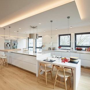 Große Moderne Wohnküche mit Unterbauwaschbecken, flächenbündigen Schrankfronten, weißen Schränken, Küchengeräten aus Edelstahl, hellem Holzboden, Kücheninsel und Küchenrückwand in Weiß in Frankfurt am Main