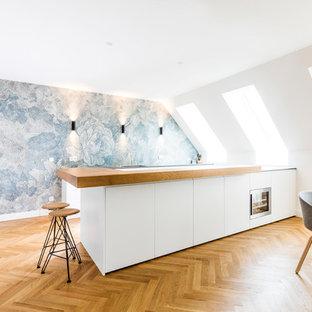 Große Skandinavische Wohnküche in L-Form mit flächenbündigen Schrankfronten, weißen Schränken, Arbeitsplatte aus Holz, hellem Holzboden, Kücheninsel, beigem Boden, beiger Arbeitsplatte, bunter Rückwand und Küchengeräten aus Edelstahl in München