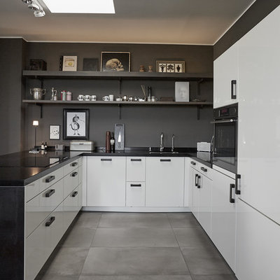 Small trendy u-shaped concrete floor and gray floor open concept kitchen photo in Berlin with a drop-in sink, flat-panel cabinets, white cabinets, brown backsplash, stainless steel appliances, a peninsula and black countertops