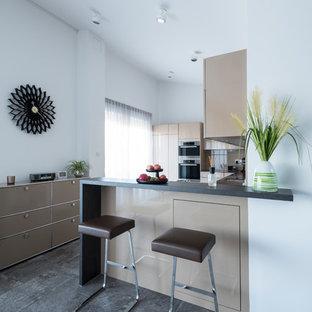 Offene, Kleine Moderne Küche in L-Form mit flächenbündigen Schrankfronten, braunen Schränken, schwarzen Elektrogeräten, Halbinsel, grauem Boden und schwarzer Arbeitsplatte in Nürnberg