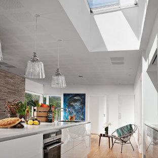 Offene, Zweizeilige Moderne Küche mit integriertem Waschbecken, flächenbündigen Schrankfronten, weißen Schränken, schwarzen Elektrogeräten, braunem Holzboden, Kücheninsel, braunem Boden und weißer Arbeitsplatte in Düsseldorf