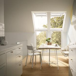 Geschlossene, Zweizeilige, Kleine Nordische Küche ohne Insel mit integriertem Waschbecken, flächenbündigen Schrankfronten, weißen Schränken, Küchenrückwand in Weiß, Rückwand aus Keramikfliesen, hellem Holzboden, braunem Boden und weißer Arbeitsplatte in Düsseldorf