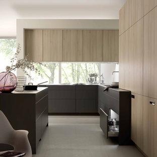 Imagen de cocina en L, minimalista, de tamaño medio, abierta, con armarios con paneles lisos, puertas de armario de madera clara y una isla