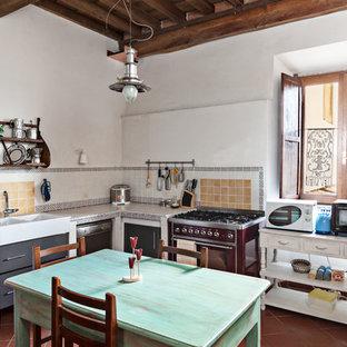 Ispirazione per una cucina country con lavello integrato, paraspruzzi con piastrelle in ceramica e pavimento in terracotta