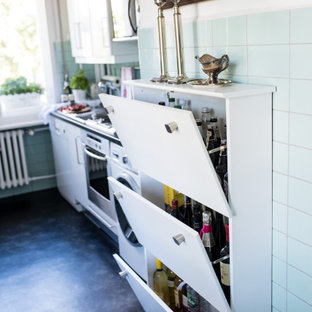 ベルリンの中サイズのエクレクティックスタイルのおしゃれなキッチン (ドロップインシンク、白いキャビネット、木材カウンター、緑のキッチンパネル、セラミックタイルのキッチンパネル、シルバーの調理設備の、リノリウムの床、黒い床、黒いキッチンカウンター) の写真