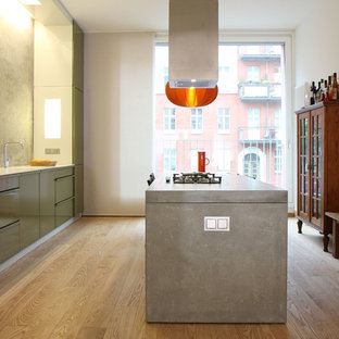 Inspiration for a large contemporary single-wall eat-in kitchen in Berlin with a single-bowl sink, flat-panel cabinets, green cabinets, concrete benchtops, grey splashback, panelled appliances, medium hardwood floors and with island.