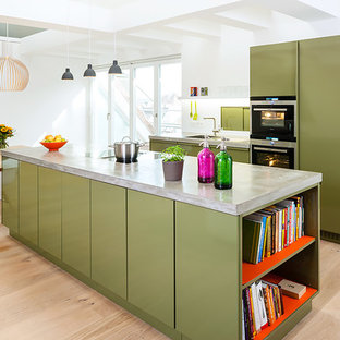 Photo of a large contemporary single-wall open plan kitchen in Berlin with a drop-in sink, flat-panel cabinets, green cabinets, concrete benchtops, white splashback, panelled appliances, light hardwood floors, with island and brown floor.