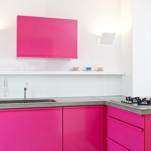 Mittelgroße Moderne Küche mit Einbauwaschbecken, flächenbündigen Schrankfronten, Betonarbeitsplatte, Elektrogeräten mit Frontblende und Halbinsel in Berlin