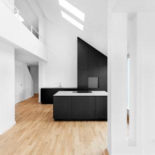 Offene, Geräumige Moderne Küche mit flächenbündigen Schrankfronten, schwarzen Schränken, Küchenrückwand in Weiß, Kücheninsel und hellem Holzboden in Berlin