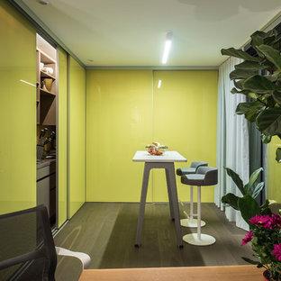 Kleine Moderne Küche in L-Form mit Vorratsschrank, flächenbündigen Schrankfronten, grünen Schränken, Elektrogeräten mit Frontblende, dunklem Holzboden, Kücheninsel und braunem Boden in Stuttgart