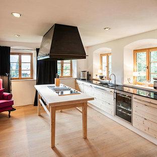 Mittelgroße Country Küche mit flächenbündigen Schrankfronten, hellen Holzschränken, Küchenrückwand in Weiß, braunem Holzboden, Kücheninsel und braunem Boden in Stuttgart