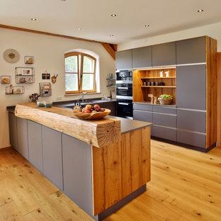 Country Küche in U-Form mit Unterbauwaschbecken, flächenbündigen Schrankfronten, grauen Schränken, schwarzen Elektrogeräten, braunem Holzboden, Halbinsel, braunem Boden und grauer Arbeitsplatte in München