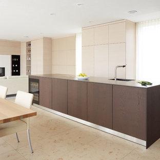 Große, Zweizeilige Moderne Wohnküche mit flächenbündigen Schrankfronten, schwarzen Elektrogeräten, Kücheninsel, beigem Boden und hellen Holzschränken in Stuttgart