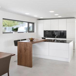 Esempio di una grande cucina abitabile minimal con ante lisce, ante bianche, paraspruzzi nero, lavello a vasca singola, elettrodomestici neri, pavimento in cemento e penisola