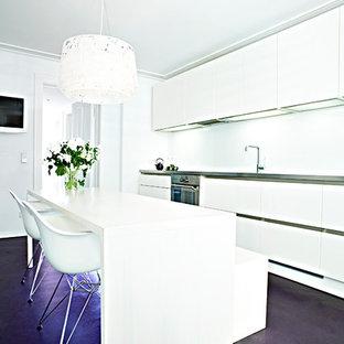 ハンブルクの小さいコンテンポラリースタイルのおしゃれなキッチン (一体型シンク、フラットパネル扉のキャビネット、白いキャビネット、ステンレスカウンター、白いキッチンパネル、ガラス板のキッチンパネル、コンクリートの床、アイランドなし、紫の床、グレーのキッチンカウンター) の写真