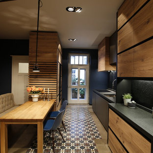 Photo of a mid-sized contemporary single-wall eat-in kitchen with a drop-in sink, flat-panel cabinets, light wood cabinets, granite benchtops, black splashback, timber splashback, black appliances, cement tiles, no island and multi-coloured floor.