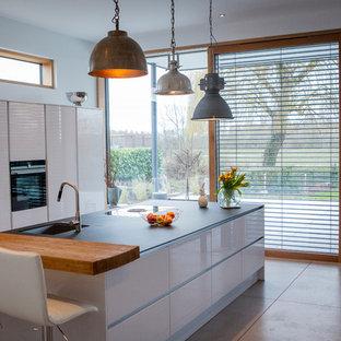 フランクフルトのインダストリアルスタイルのおしゃれなキッチン (アンダーカウンターシンク、フラットパネル扉のキャビネット、白いキャビネット、御影石カウンター、白いキッチンパネル、ガラスまたは窓のキッチンパネル、シルバーの調理設備の、セメントタイルの床、グレーの床、黒いキッチンカウンター) の写真