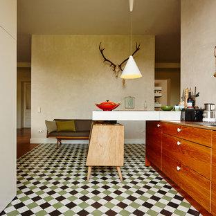 Mittelgroße Retro Küche mit flächenbündigen Schrankfronten, hellbraunen Holzschränken, Küchengeräten aus Edelstahl, Halbinsel und buntem Boden in Düsseldorf