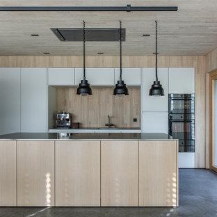 Zweizeilige Moderne Küche mit flächenbündigen Schrankfronten, weißen Schränken, Küchenrückwand in Beige, Rückwand aus Holz, Küchengeräten aus Edelstahl, Betonboden, Kücheninsel, grauem Boden und grauer Arbeitsplatte in Sonstige