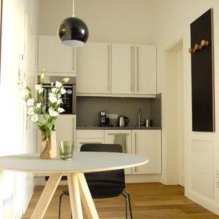 Einzeilige, Kleine Moderne Wohnküche ohne Insel mit flächenbündigen Schrankfronten, weißen Schränken, Küchenrückwand in Grau, Küchengeräten aus Edelstahl und braunem Holzboden in Berlin