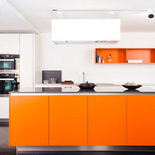 フランクフルトの大きいコンテンポラリースタイルのおしゃれなアイランドキッチン (フラットパネル扉のキャビネット、オレンジのキャビネット、コンクリートの床、シルバーの調理設備の) の写真