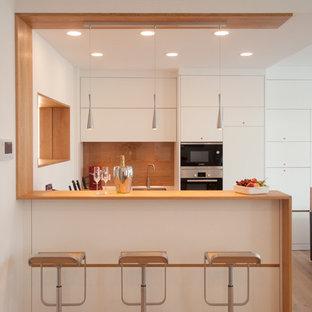 Foto de cocina en U, actual, pequeña, abierta, con fregadero bajoencimera, armarios con paneles lisos, puertas de armario blancas, suelo de madera clara, península y salpicadero marrón