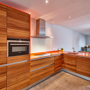 Large contemporary l-shaped eat-in kitchen in Other with an undermount sink, flat-panel cabinets, medium wood cabinets, glass sheet splashback, stainless steel appliances, solid surface benchtops, white splashback, a peninsula, concrete floors and orange benchtop.