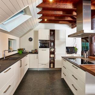 Offene Country Küche in L-Form mit Unterbauwaschbecken, Schrankfronten im Shaker-Stil, weißen Schränken, Kücheninsel, Küchenrückwand in Weiß, Quarzwerkstein-Arbeitsplatte, weißen Elektrogeräten und Betonboden in Sonstige