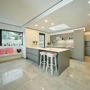 Moderne Küche in L-Form mit Unterbauwaschbecken, flächenbündigen Schrankfronten, grauen Schränken, Elektrogeräten mit Frontblende, Halbinsel, grauem Boden und weißer Arbeitsplatte in Stuttgart