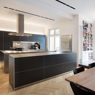 Offene, Geräumige Moderne Küche mit Doppelwaschbecken, flächenbündigen Schrankfronten, schwarzen Schränken, Edelstahl-Arbeitsplatte, Küchenrückwand in Metallic, Elektrogeräten mit Frontblende, braunem Holzboden und zwei Kücheninseln in Köln
