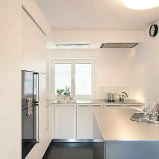Ispirazione per una piccola cucina minimal chiusa con lavello integrato, ante lisce, ante bianche, top in acciaio inossidabile, paraspruzzi bianco, paraspruzzi con lastra di vetro, elettrodomestici neri, isola e pavimento in cemento