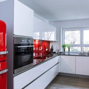 Mittelgroße Moderne Küche ohne Insel in U-Form mit integriertem Waschbecken, flächenbündigen Schrankfronten, weißen Schränken, Küchenrückwand in Rot, Glasrückwand, bunten Elektrogeräten und hellem Holzboden in München