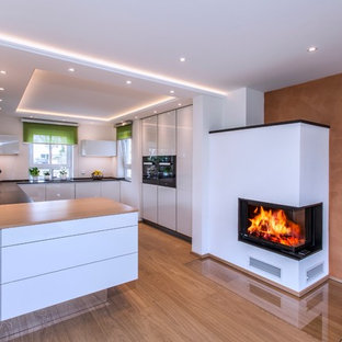 ミュンヘンの広いコンテンポラリースタイルのおしゃれなキッチン (フラットパネル扉のキャビネット、ドロップインシンク、白いキャビネット、木材カウンター、白いキッチンパネル、黒い調理設備、無垢フローリング) の写真