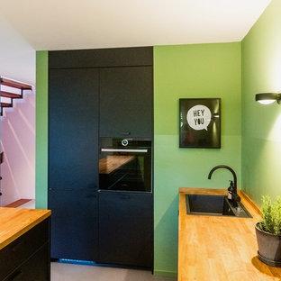 Modelo de cocina en L, contemporánea, de tamaño medio, abierta, con fregadero encastrado, puertas de armario negras, encimera de madera, salpicadero gris, electrodomésticos negros, suelo de linóleo, una isla, suelo gris y encimeras marrones