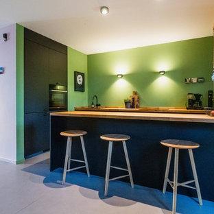Выдающиеся фото от архитекторов и дизайнеров интерьера: угловая кухня-гостиная среднего размера в современном стиле с накладной раковиной, черными фасадами, столешницей из дерева, зеленым фартуком, черной техникой, полом из линолеума, островом, серым полом и коричневой столешницей