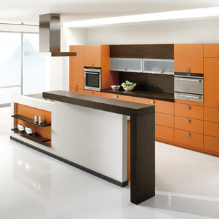 Mid-sized contemporary galley open plan kitchen in Stuttgart with a single-bowl sink, flat-panel cabinets, orange cabinets, wood benchtops, brown splashback, stainless steel appliances, vinyl floors and with island.