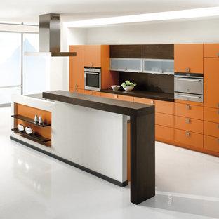 シュトゥットガルトの中くらいのコンテンポラリースタイルのおしゃれなキッチン (シングルシンク、フラットパネル扉のキャビネット、オレンジのキャビネット、木材カウンター、茶色いキッチンパネル、シルバーの調理設備、クッションフロア) の写真