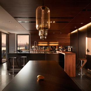 Modelo de cocina comedor contemporánea, grande, con armarios con paneles lisos, puertas de armario de madera en tonos medios, electrodomésticos de acero inoxidable, suelo de madera pintada y una isla