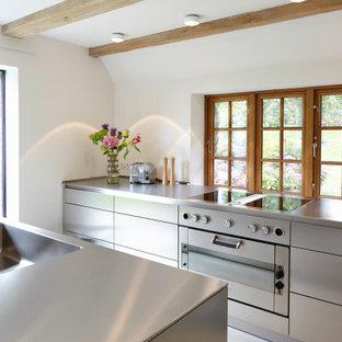 Zweizeilige Landhausstil Küche mit integriertem Waschbecken, flächenbündigen Schrankfronten, grauen Schränken, Edelstahl-Arbeitsplatte, Kücheninsel, grauem Boden, grauer Arbeitsplatte und freigelegten Dachbalken in Hamburg