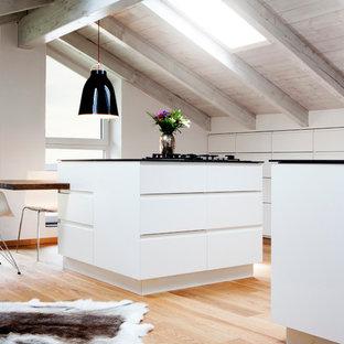 Bild på ett stort minimalistiskt kök, med släta luckor, vita skåp, ljust trägolv, flera köksöar, en integrerad diskho, bänkskiva i koppar, vitt stänkskydd, stänkskydd i trä, integrerade vitvaror och brunt golv