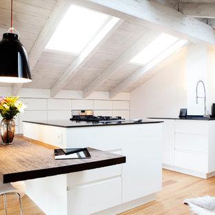 Geschlossene, Große, Zweizeilige Nordische Küche mit flächenbündigen Schrankfronten, weißen Schränken, hellem Holzboden, zwei Kücheninseln, Elektrogeräten mit Frontblende, integriertem Waschbecken, Mineralwerkstoff-Arbeitsplatte, Küchenrückwand in Weiß, Rückwand aus Holz und braunem Boden in München