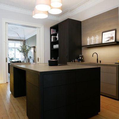 Mid-sized trendy galley medium tone wood floor and brown floor enclosed kitchen photo in Hamburg with a drop-in sink, flat-panel cabinets, black cabinets, brown backsplash, black appliances, an island and black countertops