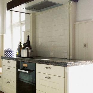 Foto på ett litet lantligt kök, med en rustik diskho, luckor med profilerade fronter, vita skåp, granitbänkskiva, vitt stänkskydd, stänkskydd i keramik, svarta vitvaror och klinkergolv i terrakotta