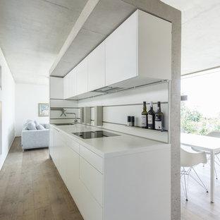 На фото: маленькая, узкая прямая кухня-гостиная в стиле модернизм с плоскими фасадами, белыми фасадами, белым фартуком и темным паркетным полом без острова с