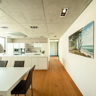Offene, Zweizeilige, Große Moderne Küche mit flächenbündigen Schrankfronten, weißen Schränken, Laminat-Arbeitsplatte, Küchenrückwand in Weiß, Kücheninsel, weißer Arbeitsplatte, Küchengeräten aus Edelstahl, braunem Holzboden, braunem Boden und Einbauwaschbecken in Stuttgart