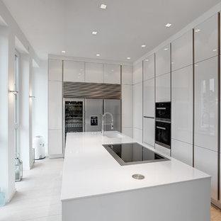 Geschlossene, Mittelgroße Moderne Küche in L-Form mit integriertem Waschbecken, flächenbündigen Schrankfronten, weißen Schränken, Küchengeräten aus Edelstahl, Kücheninsel und gebeiztem Holzboden in Köln