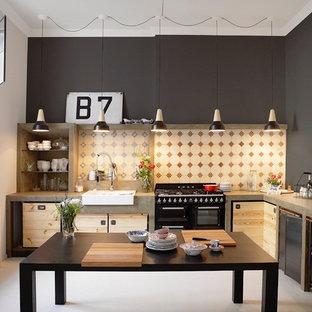 ハンブルクのインダストリアルスタイルのおしゃれなキッチン (エプロンフロントシンク、フラットパネル扉のキャビネット、マルチカラーのキッチンパネル、黒い調理設備、グレーの床) の写真