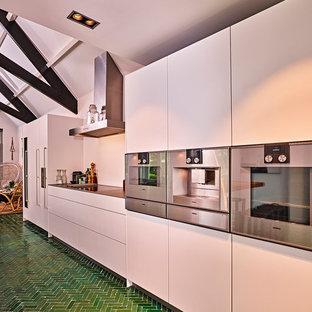 Новые идеи обустройства дома: огромная параллельная кухня в современном стиле с обеденным столом, монолитной раковиной, плоскими фасадами, белыми фасадами, столешницей из нержавеющей стали, белым фартуком, техникой из нержавеющей стали, полом из керамической плитки, островом и зеленым полом