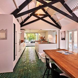 Zweizeilige, Geräumige Moderne Wohnküche mit integriertem Waschbecken, flächenbündigen Schrankfronten, weißen Schränken, Edelstahl-Arbeitsplatte, Küchenrückwand in Weiß, Küchengeräten aus Edelstahl, Keramikboden, Kücheninsel und grünem Boden in Sonstige