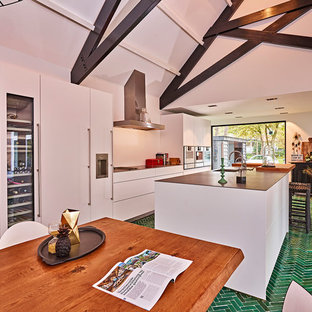 This is an example of an expansive contemporary galley kitchen/diner in Other with an integrated sink, flat-panel cabinets, white cabinets, stainless steel worktops, white splashback, stainless steel appliances, ceramic flooring, an island and green floors.